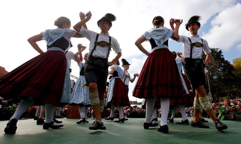 Люди танцуют в национальных немецких костюмах, фото