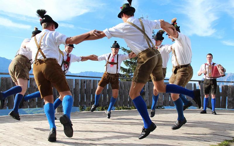 Мужчины танцуют в национальных немецких костюмах, фото
