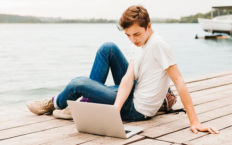 Мальчик с ноутбуком на озере, фото