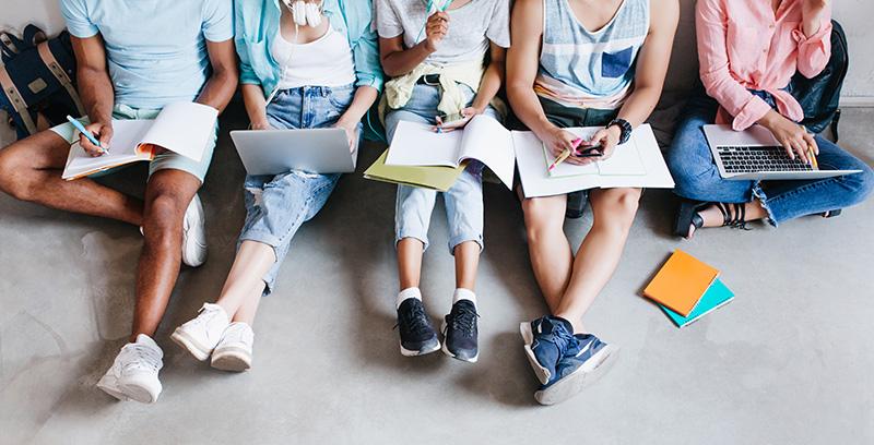 Студенты сидят на полу с тетрадями и учебниками, фото