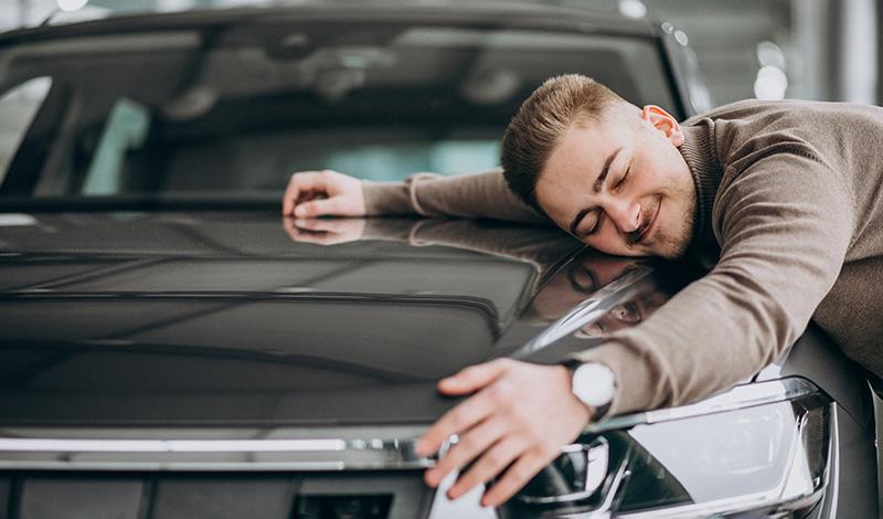Мужчина обнимает автомобиль, фото
